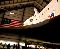 Back, right side with American flag on Endeavour and wall behind.
