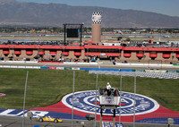Finish line, flag stand, pits, suites, and mountains beyond Fontana, California